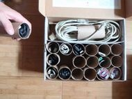 Reuse toilet paper rolls to organize cables and cords in closet