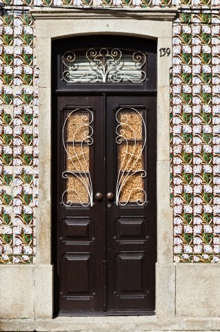 Floral motifs painted on azulejos tiles surround a traditional doorway in Ilhavo, Aveiro, Portugal