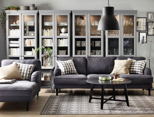 Vardagsrum med grå 3,5-sits soffa, schäslong och runt svart soffbord. Här med fyra grå vitrinskåp.
