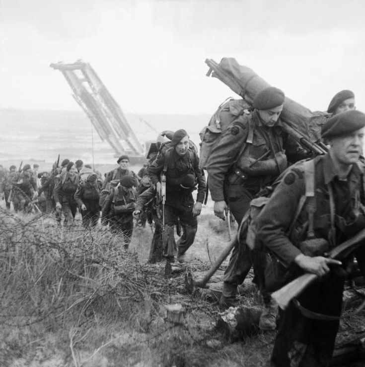 BRITISH ARMY NORMANDY 1944 (B 5071)   Royal Marine Commandos attached to 3rd Division for the assault on Sword Beach move inland, 6 June 1944. A Churchill bridgelayer can be seen in the background.
