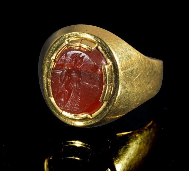 Moderner Goldring mit antiker Gemme. Gemme, römisch, 1. - 2. Jh. n. Chr. , Ring modern. 7,22g, Umfang 60mm. Schmale, nach oben breiter werdende Schiene, auf der Platte in einer zinnenartigen Fassung eine längsovale, römische Gemme aus Karneol. Auf dem Intaglio Minerva mit Lanze und Schild. Gold! 750er Gold (Stempel), winzige Splitter der Gemme fehlen. Provenienz: Ex Sammlung F.M., Bayern, 1970er Jahre. SIXBID.COM - Experts in numismatic Auctions