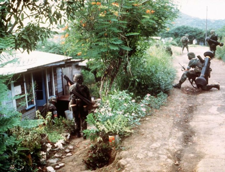 American soldiers sweep residences near Point Salinas Airfield. Some soldiers have an M47 Dragons.