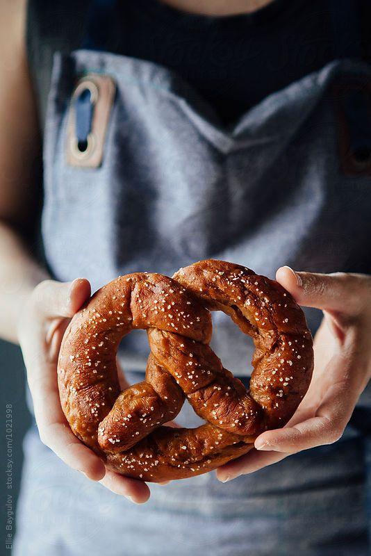 Woman holding freshly made pretzel by Ellie Baygulov for Stocksy United