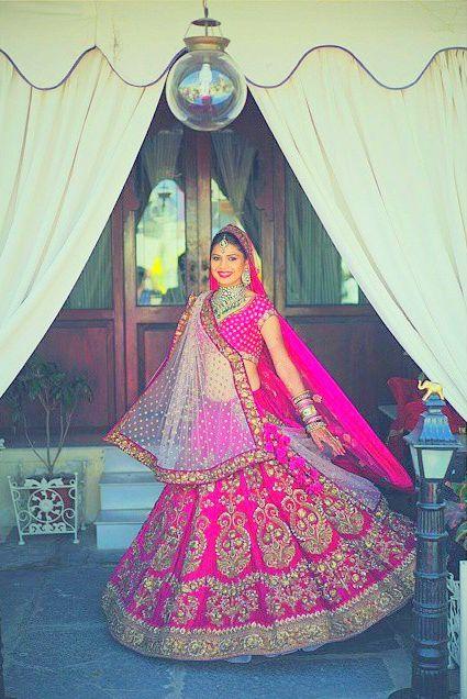 The mandatory lehenga twirl. A stunning bride wearing a fuchsia pink and gold Sabyasachi lehenga for an Udaipur wedding. Photographed by ace wedding photographer Stories by Joe Radhik of Mumbai. #Bridelan #Sabyasachi #sabyasachiweddinglehenga