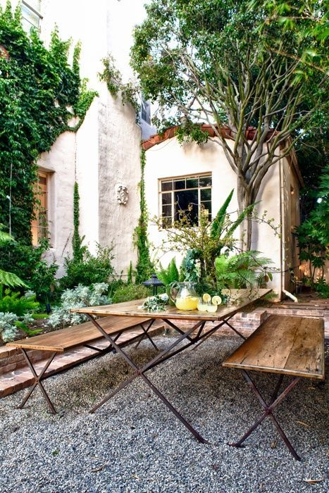 I love how the table and benches evoke the style of the house. And the crushed stone is a great alternative to pavers.
