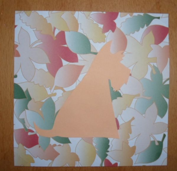 Dog picture. The dog is cut out of cardboard and then glued on some leaves patterned paper.