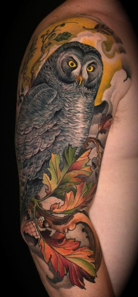 Gorgeous lifelike colored creepy owl tattoo on half sleeve with oak leaves and acorns