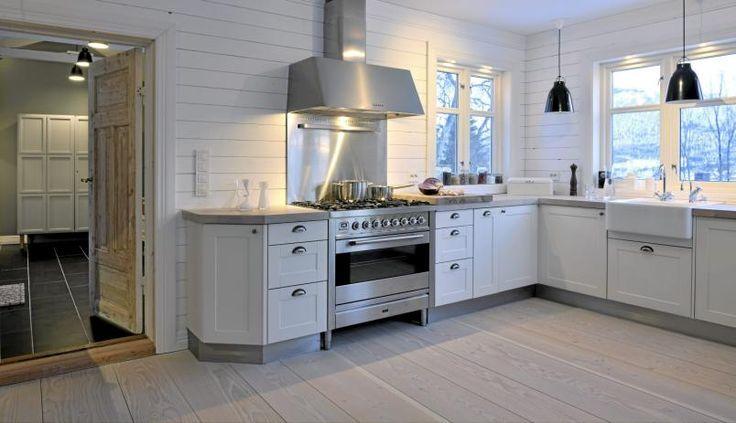 Kjøkkenet domineres av hvite vegger, tak og kjøkkenfronter. Svarte taklamper og en stålfarget gassovn og vifte skaper et maskulint og sterilt preg.