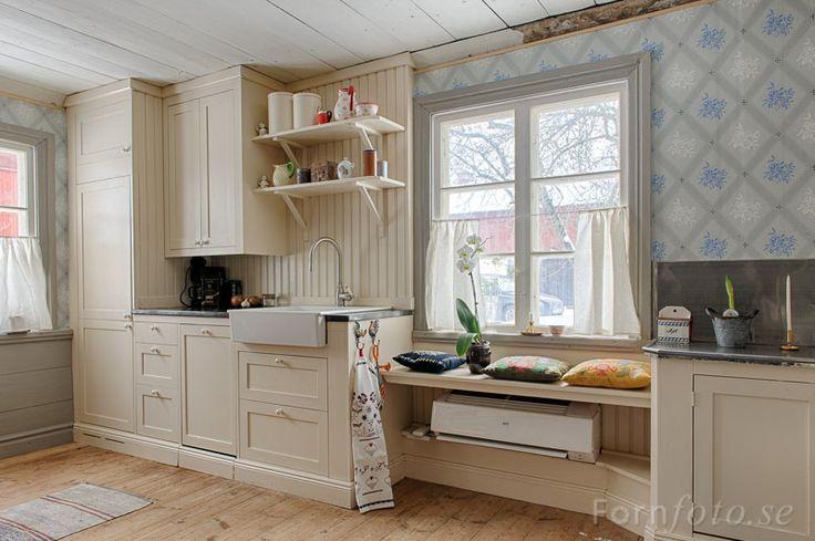 Grå bröstpanel, fönsterfoder, cremevitt kök, vitt tak och vita fönster