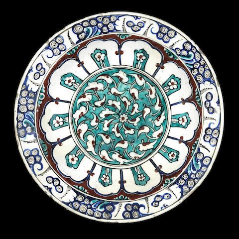 An Iznik pottery Dish - Turkey, circa 1580 - of shallow rounded form on a short foot with everted rim, decorated in raised-red, cobalt blue, turquoise and black on a white ground with a central roundel containing an interlacing arabesque whorl reserved on a turquoise ground, the cavetto with ten mihrab shaped panels containing a flower, with rock and wave border, the exterior with groups of flowers alternating with rosettes 30.3 cm. diam.