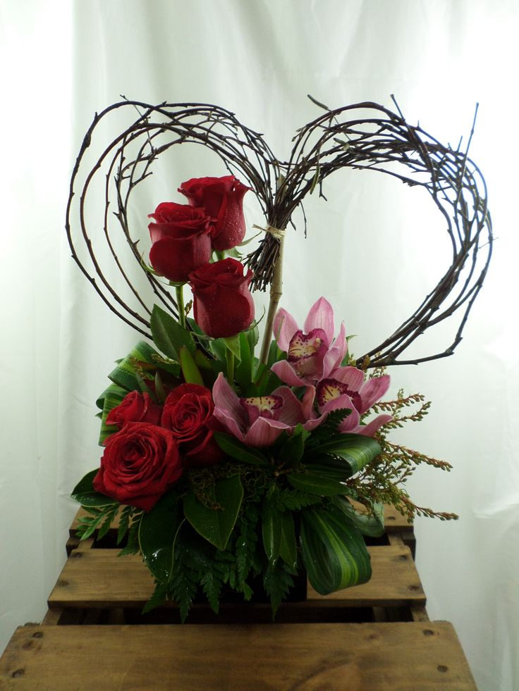 Heart shaped table arrangement made with red roses and orchids. Created by Florist ilene