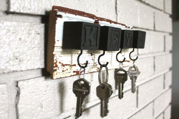 El tablero de apartadero blanco explica llaves en bloques vintage negros con taza negra ganchos para colgar tus llaves y mucho más.    Tiene un