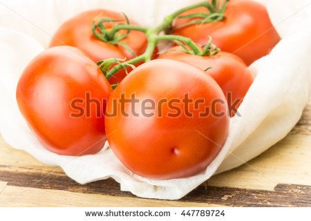 Fresh tomatoes in eco cloth bag, on wooden surface