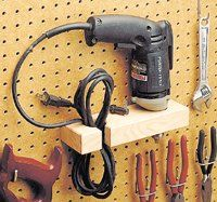 "Here's a handy way to store your electric drill — a ""holster"" that hangs on a pegboard rack. The holster is a scrap of ""two-by"" material wi..."