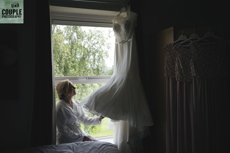 The bride sits in the window light and takes a look at her dress before putting it on. Weddings at Tulfarris Hotel & Golf Resort photographed by Couple Photography.