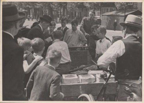 Een man noteert op de Vijzelgracht het adres van een jongen wegens diens vermeende belediging van een nationaal-socialistische vrouw. Opschrift op verso: '18 juni 1941; Een Nat Soc noteerd een Jood zijn adres na een dame beledigd te hebben'