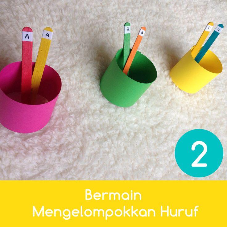 Bermain Mengelompokkan Huruf Cara membuat: 1. Potong gulungan tissue bekas menjadi 2 atau gunakan karton warna-warni Cara bermain: 1. Ajak anak untuk mengenali masing-masing warna 'keranjang' yang ada 2. Tentukan alfabet untuk masing-masing warna keranjang, misal: pink untuk huruf A dan hijau untuk B. 3. Minta anak untuk memasukkan stik alfabet ke dalam keranjangnya masing-masing.