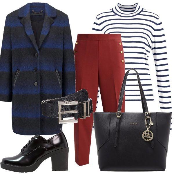 Pantalone rosso a vita alta, maglione a righe bianche e blu con collo alla coreana. Cappotto a righe sfumate blu e nero. Cintura nera abbinata ad una shopping bag e tronchetti con tacco largo.