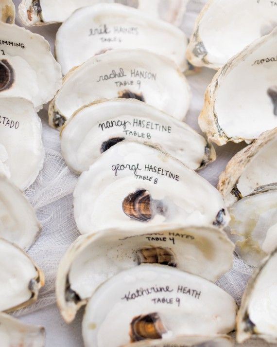 similar to the smooth stones in acquavella wedding//In the spirit of the nautical Cape Cod wedding, oyster shells hand-written with names and table numbers helped guests find their seats.