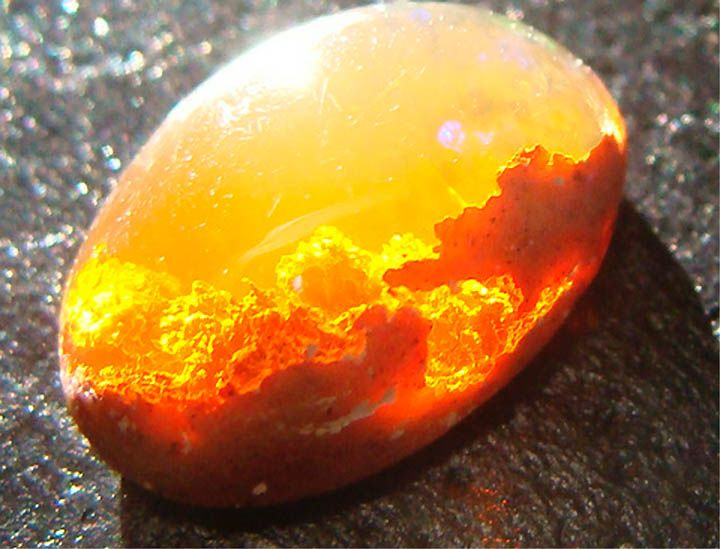 """°This is a rare """"Fire Opal"""", or Girasol, found in Mexico: almost a world in itself, emanating mysterious light ~ """"Fire opals are either faceted – that is, as far as their transparency allows – or cut as a cabochon, since this is the shape which best brings out the rich glow of this orange jewel. It is the oval which is regarded as the classical shape for valuable fire opals."""""""