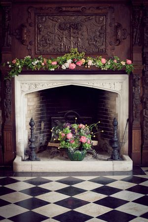 flowers in fireplace and floral garland across mantelpiece