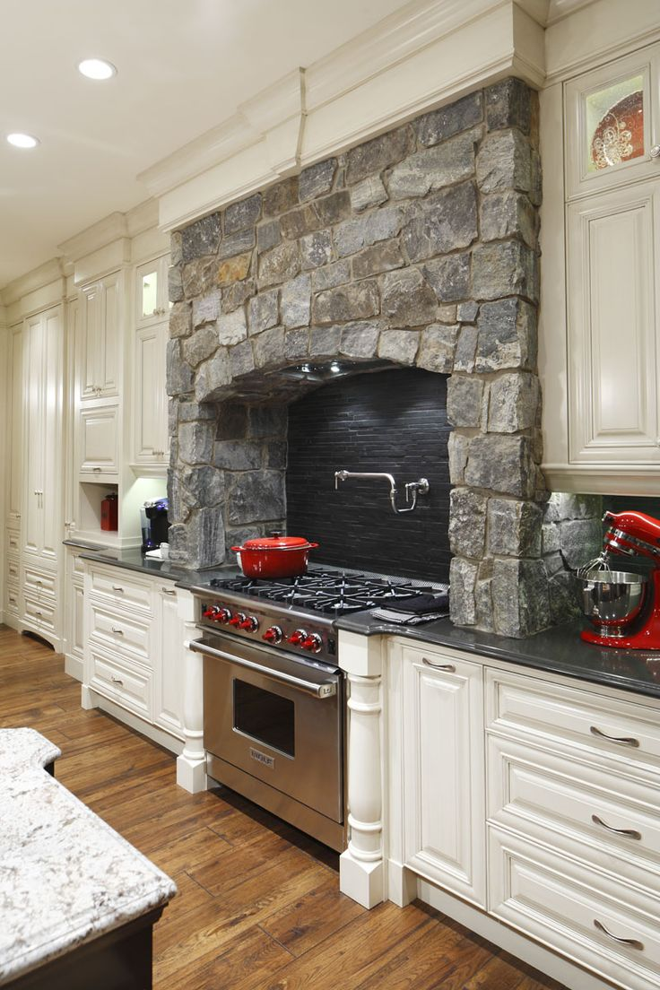 stone surrounds gas cooking stove in this traditional white kitchen