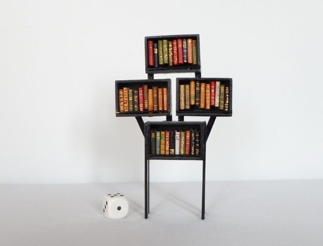 Mini-bibliothèque réalisée en balsa contenant 39 mini-livres reliés. Dé au sol donnant une idée de l'échellle