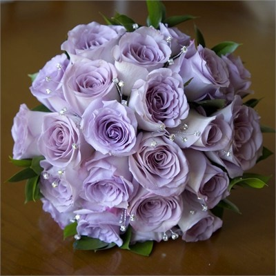 The bridal bouquet was a hand-tied posy made up of Lilac roses, also known as Ocean Song, along with crystals, leaves and ruscus, bound with white ribbon and crystal pins.  The bridesmaids carried similar bouquets which were smaller, and the grooms party wore lilac rose coloured button holes.Tall vases featuring lilac roses, lisanthus and bear grass were placed in the centre of each weddi...