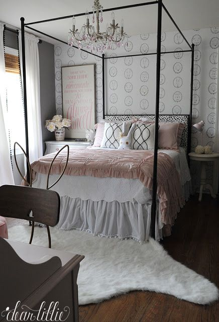 A cute little pink desk lamp and a cozy white rug both from @homegoods add fun little touches to this pink white and black little girls room. The canopy bed adds a touch of elegance and the wallpaper with portraits of bunnies, fox and other little creatures add a touch of whimsy. (sponsored pin)
