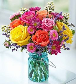 Garden Bouquet™ Capture the charm and color of the garden with this beautiful arrangement. Featuring vibrant roses, daisy poms, asters and more, and hand-designed in a reusable mason jar, it's a gift