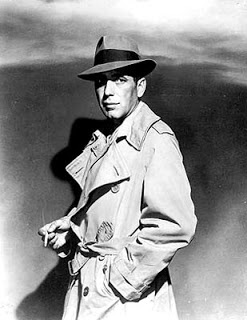 Humphrey Bogart wearing a trench and a fedora hat in Casablanca