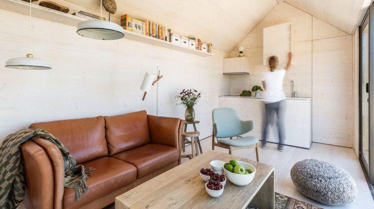 Casa modular transportable APH80: estructura fabricada con CNC, exterior de paneles de viruta e madera revestido con cemento, interior de paneles de abeto tintados en blanco