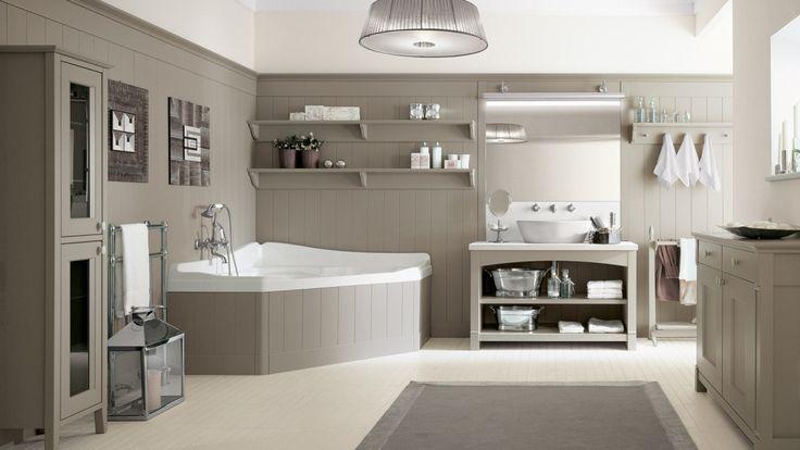 La finitura Grigio Argilla coordina tutti gli elementi del bagno: il mobile con base a giorno sormontato dal lavello, il mobile contenitore e la vasca angolare in vetroresina rivestita con pannelli dogati.