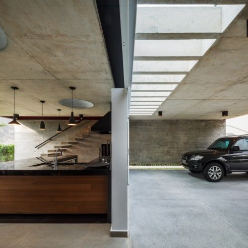 Churrasqueira e garagem são separadas por uma parede simples de alvenaria na casa Planalto, com projeto assinado por Flavio Castro. Tanto de um lado quanto do outro, a entrada de luz natural pelo forro de concreto se dá através de claraboias