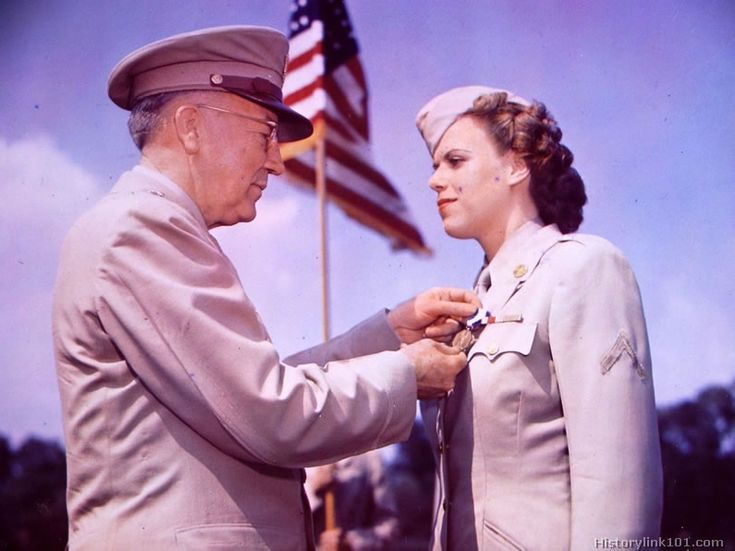 Major General, the chief signal officer, US Army pins the soldiers medal on WAC PFC. at Fort Myer, VA for risking her life in attempting to ...