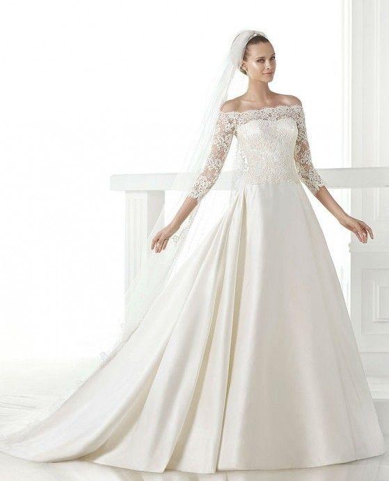 Cette robe Celandia d'Atelier Pronovias superpose un haut en dentelle sur une robe bustier sobre. Les manches trois-quarts dénudent les épaules juste ce qu'il faut.