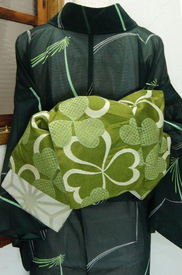 渋みのあるおだやかな緑で織り出された大胆な麻の葉文様に、愛らしいカタバミの葉模様が重ねられたレトロモダンな半幅帯です。 #kimono