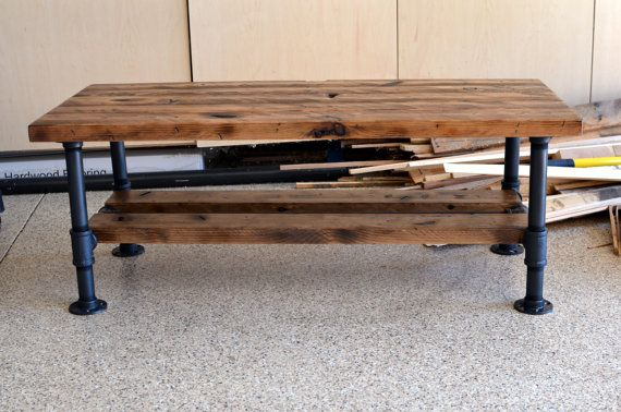 Distressed Knotty Pine Coffee Table with Steel Pipe Legs and a Lower Wood Shelf