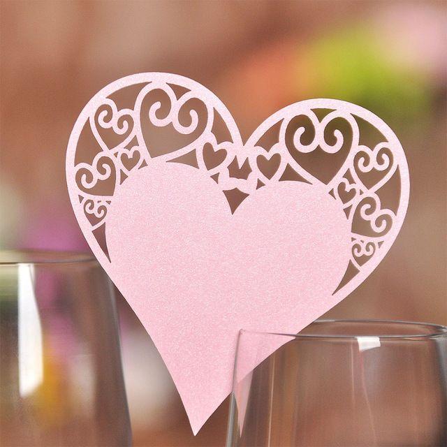 Flotte lyserøde hjerteformede bordkort til glas med et romantisk topmønster.
