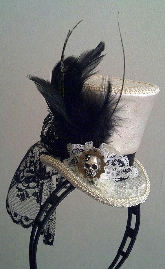 Mini sombrero de copa en marfil y negro. Cráneo del azúcar de metal y pieza de engranaje lateral. Hecho a mano sobre su orden. Nuestro diseño está en una banda de la cabeza negro, blanco o marrón o pinza de pelo de metal pequeño de fácil desgaste, por favor especificar en el pedido. Satén, encaje y telas finas en USA. Todo hecho a mano y nuestro diseño. Descuento en múltiples sombreros. Tenga en cuenta que este estilo de sombrero puede ser ocasiones colores personalizados que usted lo…
