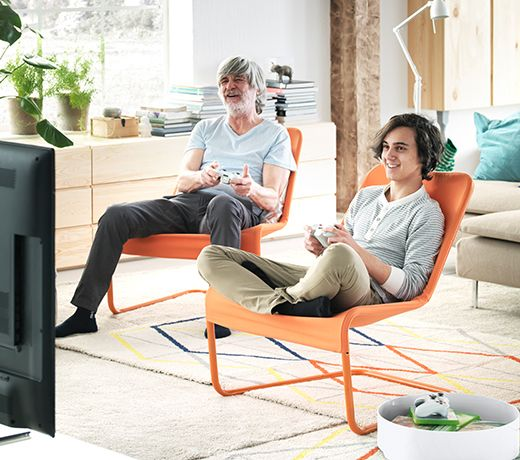 Grandfather And Grandson Sitting On IKEA Easy Chairs Playing A Video Game Together LOCKSTA