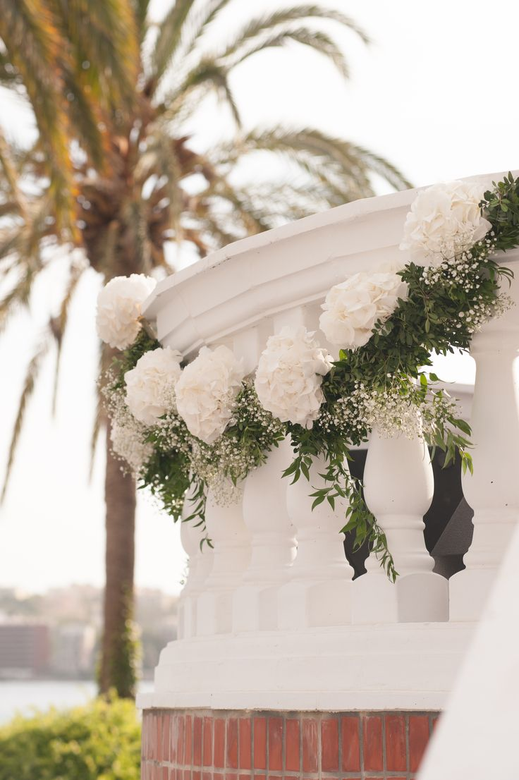 Hanging garlands adorning the hotel bannisters overlooking the ceremony Photography by Thomas Barr