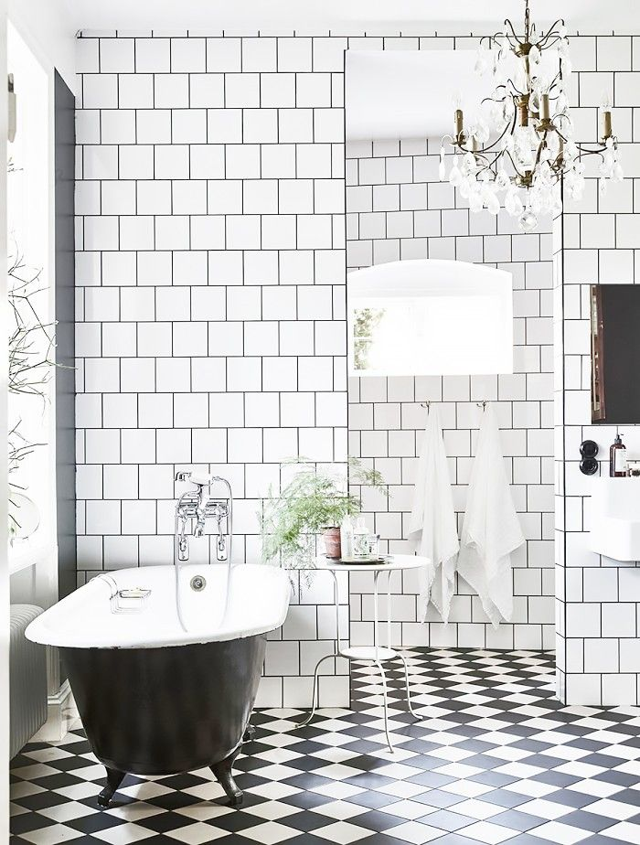 Tired of classic subway tiles? This square Scandinavian variation could be the next big thing. The square tiles work well with this traditional bathtub and black-and-white checkerboard floor tiles, giving the room an elegant monochrome theme.