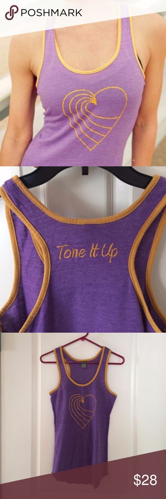 Purple + Gold Logo Heart Tank Top A must-have item for the TIU Beach Babe! Logo on front with golden yellow border set to a solid grape purple. Ideal for working out and casual days. New without tags! Polyester, cotton and rayon blend. Retired style. Measurements upon request. Rounded hem. Offers always considered. Tone It Up Tops Tank Tops