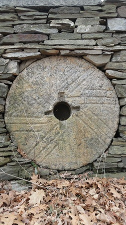 Old grist mill stone set in a stone wall.