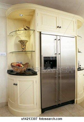 Stainless-steel American-style fridge freezer built into cream kitchen unit with glass corner shelves View Large Photo Image