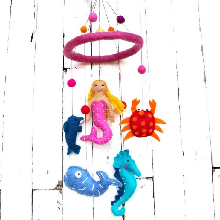 Cute felt mobile for little girls depicting various underwater animals (and our gorgeous mermaid) suspended on solid round felted ring. There are 5 individual pieces, the center mermaid being on a shorter string.Our felt Under The Sea mobile comes ready to hang on quality plaited string.FIBRE: Hand felted WOOL (from Australia