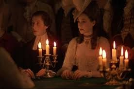 MOTIVATING LIGHTING  In this scene we can see it is being lit by a series of candles set in old fashioned candleholders. The fact that they're close to the characters faces creates an 'up light' sort of effect, making the mood and scene more dramatic. It could be a suspenseful moment which is why the darkness of the scene is used but is lit slightly by a few burning candles.