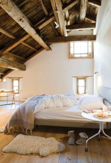 Schlafzimmer unter dem Dach mit Holz, hoher Raumhöhe und kleinen Fenstern.