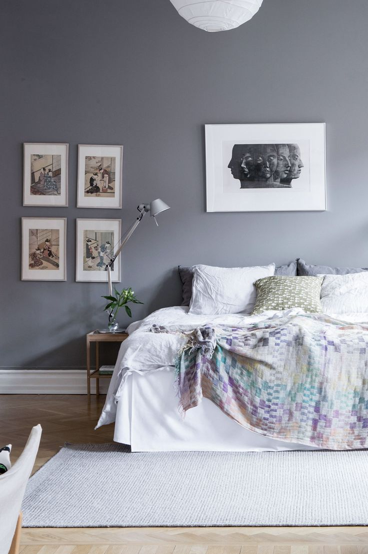Scandinavian decoration and ideas. Bedroom with grey painted walls and art. Cozy bedding.
